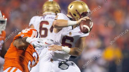 Stock Photo of Boston College quarterback Dennis Grosel (6) avoids a tackle by Clemson defensive end Xavier Thomas (3) during the first half of an NCAA college football game, in Clemson, S.C