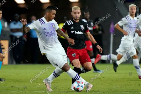 Orlando City defender Antonio Carlos, left, moves the ball away from D.C. United midfielder Felipe Martins during the second half of an MLS soccer match, in Orlando, Fla