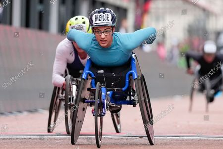Germany's Merle Menje crosses the finish line to take second place ahead of United States' Tatyana Mcfadden, background left, in the Women's wheelchair race in the London Marathon in central London