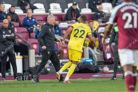 West Ham United Manager David Moyes and Mathias Jorgensen of Brentford FC appear to exchange heated words