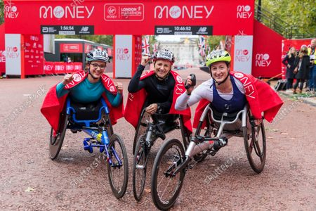 Switzerland's Manuela Schar (C) celebrates winning the women's wheelchair race with second placed Germany's Merle Menje (L) and third placed Tatyana McFadden (R) of the US at the 2021 London Marathon in London, Britain, 03 October 2021.