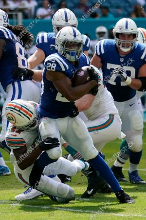 Indianapolis Colts running back Jonathan Taylor (28) is brought down by Miami Dolphins cornerback Justin Coleman (27), left, and Miami Dolphins outside linebacker Andrew Van Ginkel (43) during the second half of an NFL football game, in Miami Gardens, Fla