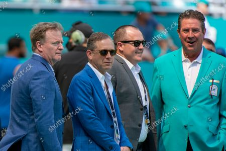 Roger Goodell (left), Bruce Beal (2nd from left) and Dan Marino (right) watch the players warm up on the field before the start of an NFL football game against the Miami Dolphins, in Miami Gardens, Fla