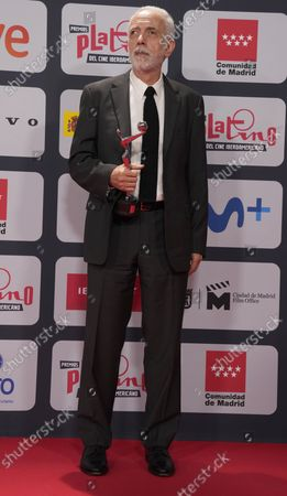 Stock Photo of Spanish director Fernando Trueba poses with his Best Picture award during the red carpet event of the Platino Awards, Ibero-America's annual film awards, outside the Palacio Municipal de Congresos de Madrid, Spain
