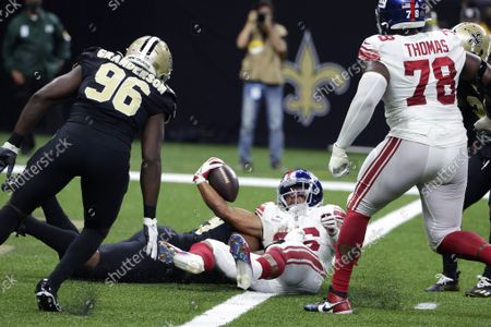 New York Giants running back Saquon Barkley (26) scores a touchdown against New Orleans Saints defensive end Carl Granderson (96) and defensive tackle Shy Tuttle to win in overtime during an NFL football game in New Orleans, . The Giants won 27-21
