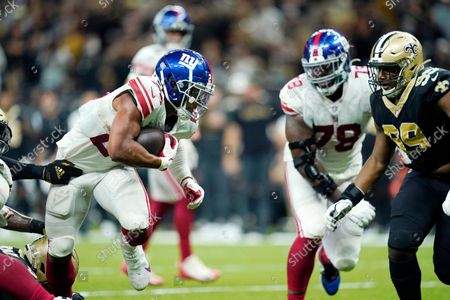 New York Giants running back Saquon Barkley carries for a touchdown to defeat the New Orleans Saints in overtime during an NFL football game in New Orleans, . The Giants won 27-21