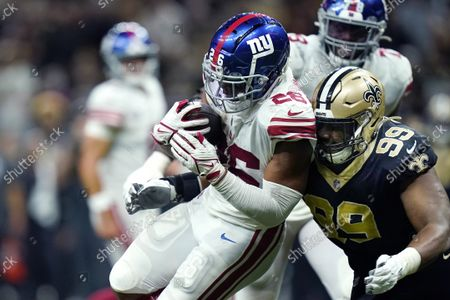 New York Giants running back Saquon Barkley carries for a touchdown against New Orleans Saints defensive tackle Shy Tuttle (99) to defeat the Saints in overtime during an NFL football game in New Orleans, . The Giants won 27-21