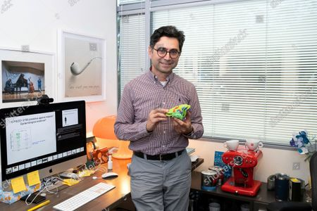 Ardem Patapoutian poses for a portrait in his office while holding a model of the Piezo protein at the Dorris Neuroscience Center, in San Diego. Two scientists, Americans Patapoutian and David Julius, won the Nobel Prize in medicine for their discoveries into how the human body perceives temperature and touch