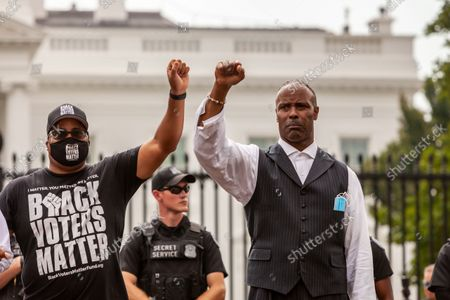 Black Voters Matter co-founder Cliff Albright and Pastor Lewis Logan raise their fists as they await arrest by the United States Secret Service during a civil disobedience action for voting rights at the White House.  Activists are demanding that the Biden Administration take the lead on voting rights and pressure Congress to pass legislation protecting the right to vote.