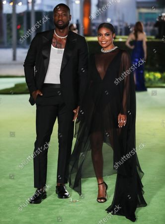 Former professional basketball player Dwyane Wade wearing a Gucci suit and Tiffany & Co. jewelry and wife/actress Gabrielle Union wearing an Alexandre Vauthier dress, Le Vian earrings, a Kallati bracelet, and Djula ring arrive at the Academy Museum of Motion Pictures Opening Gala held at the Academy Museum of Motion Pictures on September 25, 2021 in Los Angeles, California, United States.