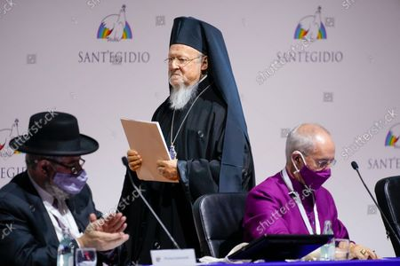 """Ecumenical Patriarch of Constantinople Bartholomew I, center, passes by President of the Conference of European Rabbis Pinchas Goldschmidt, left, and Archbishop of Canterbury Justin Welby, as he prepares to deliver his speech at the interreligious meeting 'Brother peoples, future land"""" organized by the Sant'Egidio Community at 'La Nuvola' (the cloud) convention center in Rome"""