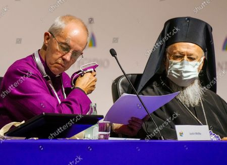 """Archbishop of Canterbury Justin Welby, left, prepares to deliver his speech as Ecumenical Patriarch of Constantinople Bartholomew I looks on at the interreligious meeting 'Brother peoples, future land"""" organized by the Sant'Egidio Community at 'La Nuvola' (the cloud) convention center in Rome"""