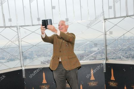 """Bobby Valentine takes a selfie with his phone at the 86th floor observatory of the Empire State Building. Former New York Mets baseball player and manager, Stamford mayoral candidate, Bobby Valentine visits the Empire State Building to honor """"Answer The Call"""" NYPD & NYFD Children's Benefit Fund, in New York City."""