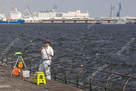 A fisherman adjusts his fishing rod at the water front inside Rinko Park in Yokohama.