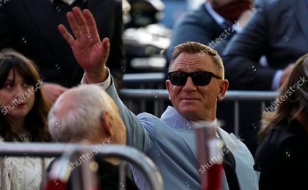 Actor Daniel Craig waves to the crowd during a ceremony to award him a star on the Hollywood Walk of Fame, in Los Angeles