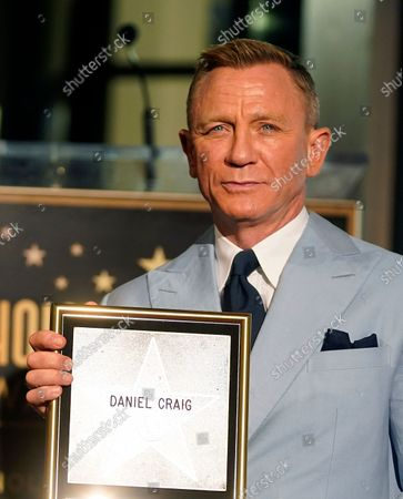 Daniel Craig poses with a replica of his new star on the Hollywood Walk of Fame during a ceremony in his honor, in Los Angeles