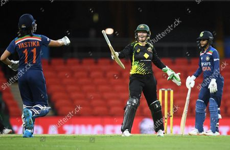 Stock Picture of Australian wicket keeper Alyssa Healy (C) hands back the bat to Yastika Bhatia (L) of India during Game 1 of the Women's T20 International Series cricket match between Australia and India at Metricon Stadium in Gold Coast, Australia, 07 October 2021.
