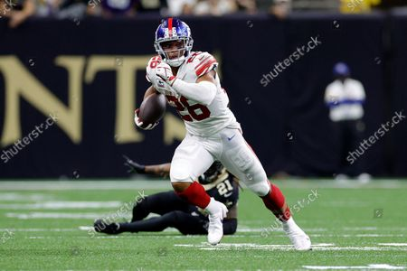 New York Giants running back Saquon Barkley (26) runs past New Orleans Saints cornerback Bradley Roby (21) during an NFL football game, in New Orleans