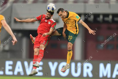 Oman's Abdulaziz Al-Muqbali, left, fights for the ball with Australia's Trent Sainsbury during a FIFA World Cup group B qualifying soccer match between Australia and Oman in Doha, Qatar