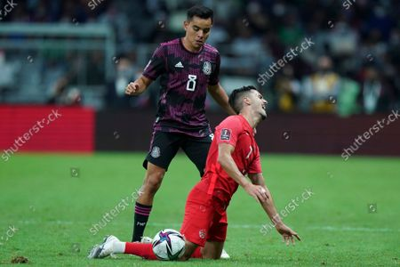 Canada's Stephen Eustaquio, below, and Mexico's Carlos Alberto Rodriguez battle for the ball during a qualifying soccer match for the FIFA World Cup Qatar 2022, at Azteca stadium in Mexico City