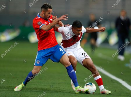 Peru's Edison Flores, right, and Chile's Mauricio Isla battle for the ball during a qualifying soccer match for the FIFA World Cup Qatar 2022 at the National stadium in Lima, Peru