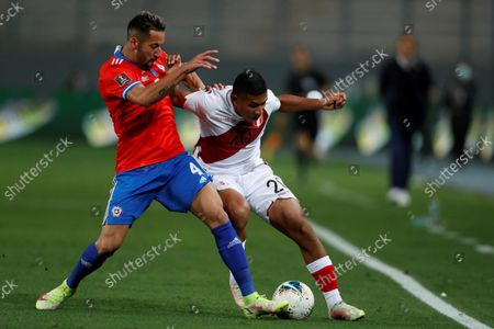 Peru's Edison Flores (R) in action against Chile's Mauricio Isla, during a soccer match between Peru and Chile amid the South American qualifiers for the Qatar 2022 World Cup at the National Stadium in Lima, Peru, 07 October 2021.