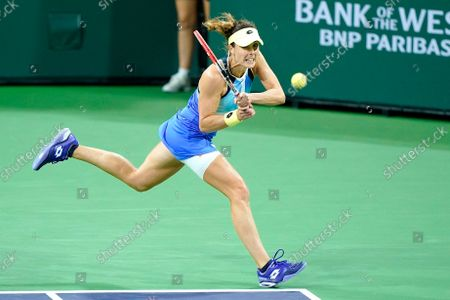Alize Cornet, of France, returns shot to Leylah Fernandez at the BNP Paribas Open tennis tournament, in Indian Wells, Calif