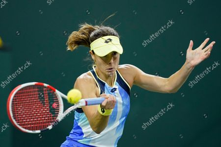 Alize Cornet, of France, returns a shot to Leylah Fernandez at the BNP Paribas Open tennis tournament, in Indian Wells, Calif