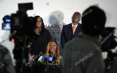 """Stock Picture of Faith Rodgers, bottom center, who testified recently at R. Kelly's criminal trial in New York, addresses reporters alongside her parents Kelly, left, and Charles, at attorney Gloria Allred's offices in Los Angeles. Rodgers addressed comments made by Bill Cosby's spokesperson, Andrew Wyatt, that Kelly was """"railroaded"""" and did not receive a fair trial"""