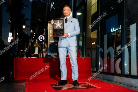 Stock Picture of British actor Daniel Craig stands atop his new star on the Hollywood Walk of Fame while holding a replica of the star during a ceremony in his honor