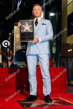 British actor Daniel Craig stands atop his new star on the Hollywood Walk of Fame while holding a replica of the star during a ceremony in his honor