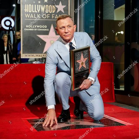 British actor Daniel Craig kneels atop his new star on the Hollywood Walk of Fame while holding a replica of the star during a ceremony in his honor