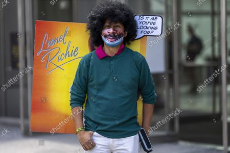 An attendee dressed as a Lionel Richie album cover poses during New York Comic Con at the Jacob K. Javits Convention Center, in New York