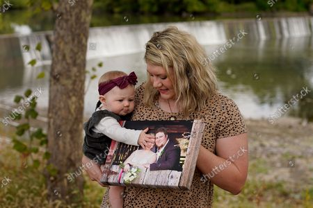 Stock Image of Aubrea Baker displays her wedding photo as she and her 7-month-old daughter Haylen visit one of her late husband's favorite fishing spots, in Burlington, Kan. Her husband, Danny Baker, was among the 700,000 U.S. victims of COVID-19, dying on Sept. 14, after testing positive in July