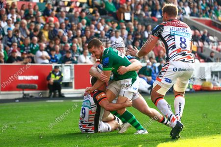 Paddy Jackson of London Irish tackled by Ben Youngs and Nic Dolly of Leicester Tigers; Brentford Community Stadium, Brentford, London; Gallagher Premiership Rugby, London Irish versus Leicester Tigers.