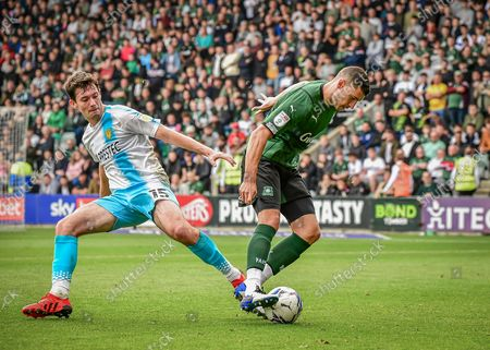 Plymouth Argyle defender James Wilson  (5) shields the ball from Burton Albion midfielder Thomas O'Connor  (15)  during the EFL Sky Bet League 1 match between Plymouth Argyle and Burton Albion at Home Park, Plymouth