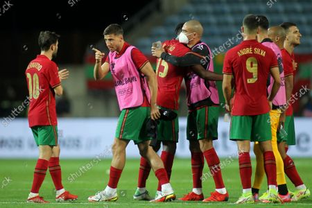 Portugal's Ruben Dias points at teammate Bernardo Silva, left, at the end of the international friendly soccer match between Portugal and Qatar at the Algarve stadium outside Faro, Portugal, . Portugal won 3-0