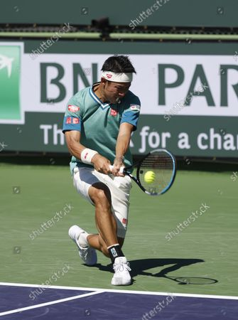 Stock Picture of Kei Nishikori of Japan returns a shot against Dan Evans of Great Britain during the BNP Paribas Open at Indian Wells Tennis Garden in Indian Wells, California. Mandatory Photo Credit : Charles Baus/CSM
