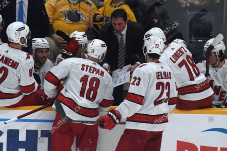 Carolina Hurricanes head coach Rod Brind'Amour, cneter top, talks to his team during a timeout in the third period of a preseason NHL hockey game against the Nashville Predators, in Nashville, Tenn
