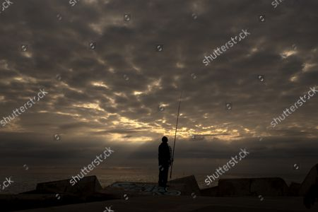 Man looks at his fishing rod on a breakwater in front of the mediterranean sea in Barcelona, Spain