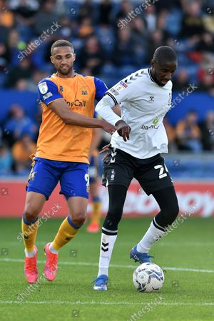 Oldham Athletic's Dylan Bahamboula tussles with Jordan Bowery of Mansfield Town during the Sky Bet League 2 match between Mansfield Town and Oldham Athletic at the One Call Stadium, Mansfield on Saturday 9th October 2021.