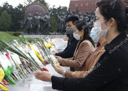 Stock Photo of Citizens lay bouquets of flowers before the statues of North Korean leaders Kim Il Sung and Kim Jong Il on the occasion of the 76th founding anniversary of the Worker's Party in Pyongyang, North Korea