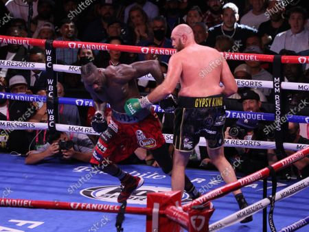 A Tyson Fury punch sends Deontay Wilder staggering during the Tyson Fury vs Deontay Wilder III 12-round Heavyweight boxing match, at the T-Mobile Arena in Las Vegas, Nevada on Saturday, October 9th, 2021.
