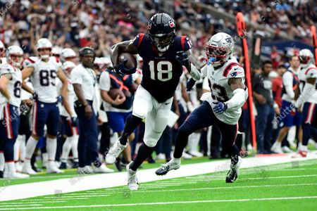 Houston Texans wide receiver Chris Conley (18) catches a pass for a first down as New England Patriots safety Kyle Dugger (23) defends during the first half of an NFL football game, in Houston
