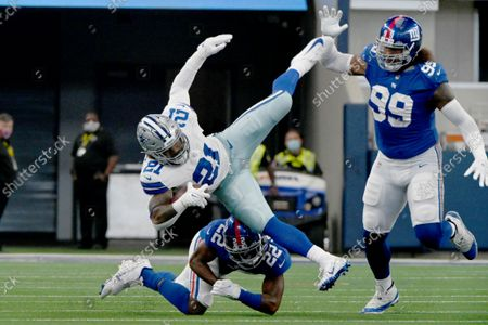 Stock Picture of Dallas Cowboys running back Ezekiel Elliott (21) is upended by New York Giants cornerback Adoree' Jackson (22) on in the first half of an NFL football game in Arlington, Texas