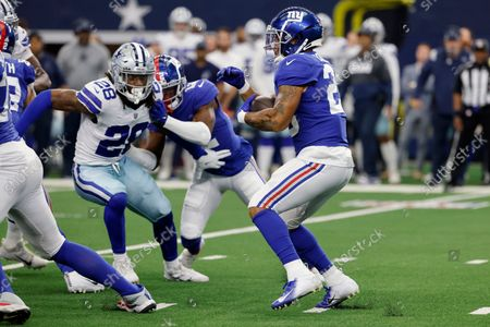 Stock Photo of Dallas Cowboys safety Malik Hooker (28) defends as New York Giants running back Saquon Barkley (26) runs then ball in the first half of an NFL football game in Arlington, Texas
