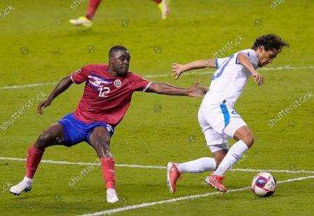 El Salvador's Enrico Duenas, right, and Costa Rica's Joel Campbell battle for the ball during a qualifying soccer match for the FIFA World Cup Qatar 2022 at National stadium in San Jose, Costa Rica