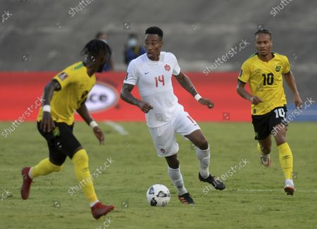 Canada's Mark Anthony Kaye, center, fights for the ball against Jamaica's Bobby Reid, right, and Oniel Fisher during a qualifying soccer match for the FIFA World Cup Qatar 2022 at the Independence Park stadium in Kingston, Jamaica