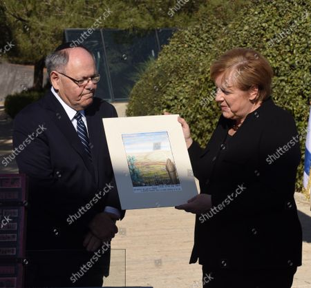 Stock Image of German Chancellor Angela Merkel (R) receives a gift from the Yad Vashem Chairman Dani Dayan at the Yad Vashem World Holocaust Center in Jerusalem, on Sunday, October 10, 2021.