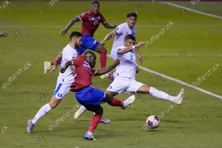 Costa Rica's Joel Campbell, front, strikes the ball as El Salvador's Roberto Dominguez blocks the shot during a qualifying soccer match for the FIFA World Cup Qatar 2022 at the National Stadium in San Jose, Costa Rica